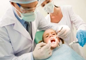Image of dental checkup being given to little girl by dentist with assistant near by