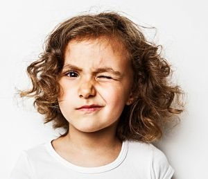little girl winks on white background