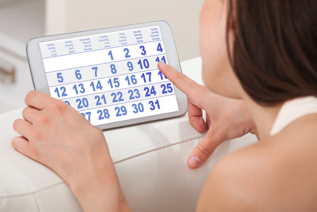 Woman Using Calendar On Digital Tablet At Home