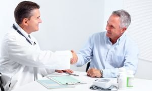 Smiling medical doctor with senior man. Health care.