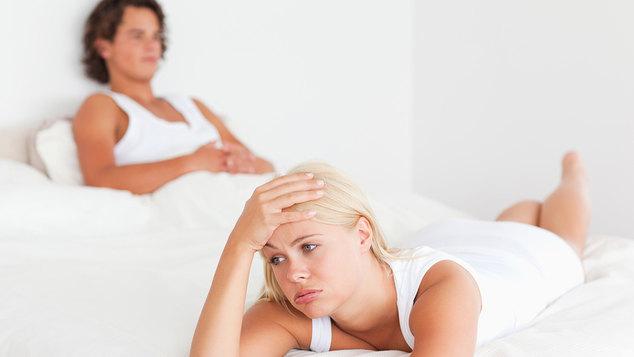 Молодой мужчина дремлет, а его девушка лежит с головной болью, прислонив руку к голове
