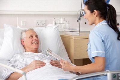 Медсестра у постели пожилого пациента